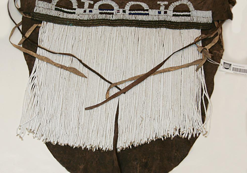 Semcircular brown leather garment with strings of white beads hanging down and ties that would fasten the garment to the body.