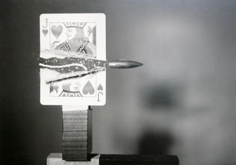 Black and white photograph of a bullet cutting a playing card in half. The bullet seems frozen in time and the card halves have not yet had time to fall. This was a feat of high speed photography at the time.