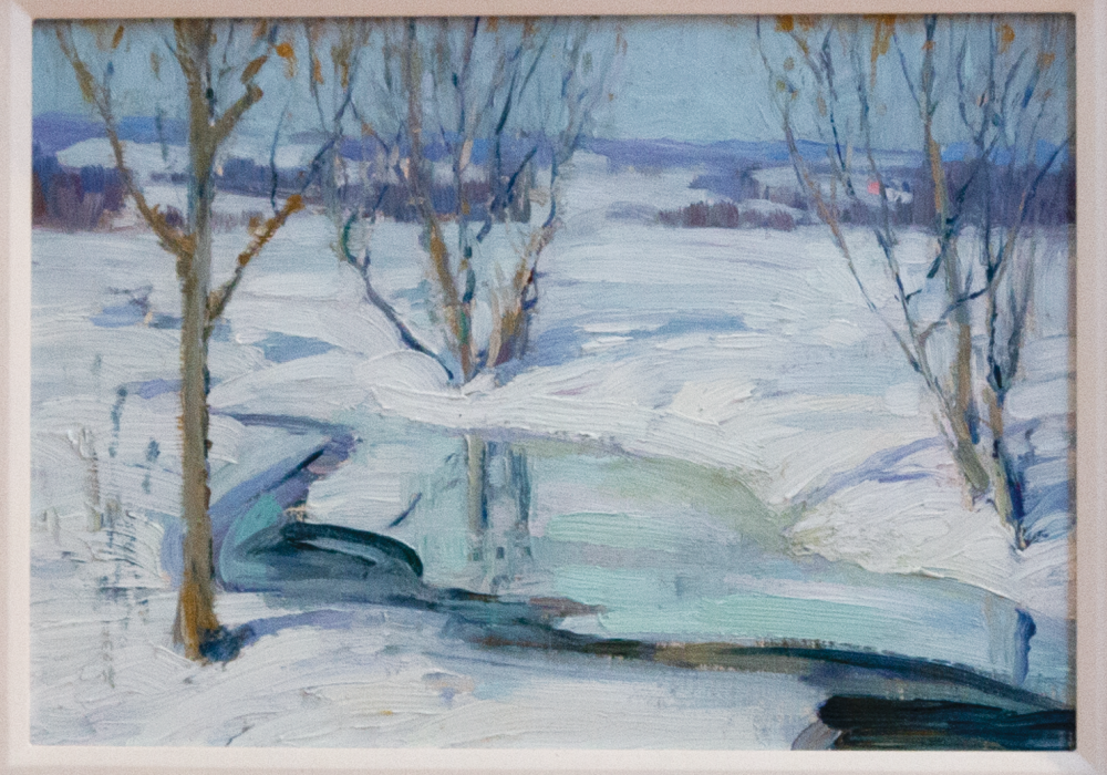 In this painting, the ground is snow covered and the trees are bare, except for a few dry leaves fluttering in the wind. The stream looks icy, and the distant landscape cold. There are only mild shadows because of the dimmer sun of a winter day.