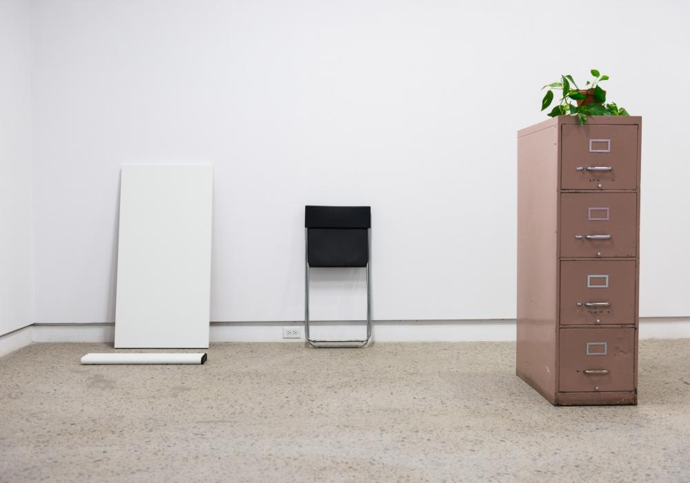 Material supports for Autumn Knight's Documents performance, including table, potted plant, chair, filing cabinet.