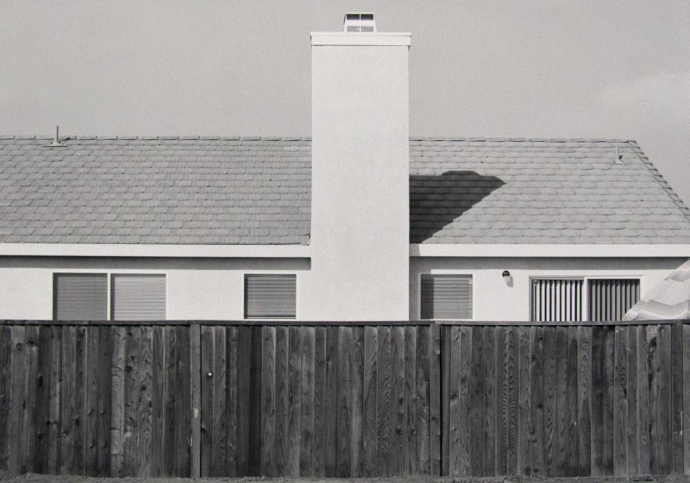 Richard Meisinger (b. 1945), Edge Effects: Fence with Rooftop and Rectangular Chimney, 1993. Photographic print. Gift of the artist 2018-3-10