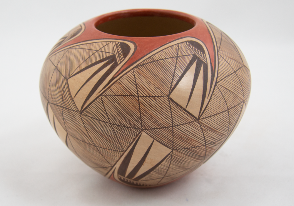 Round, buff-colored ceramic jar with fine hatching patterns in black over much of its surface. The circular opening has red pigment that swoops down into the strongly geometric design