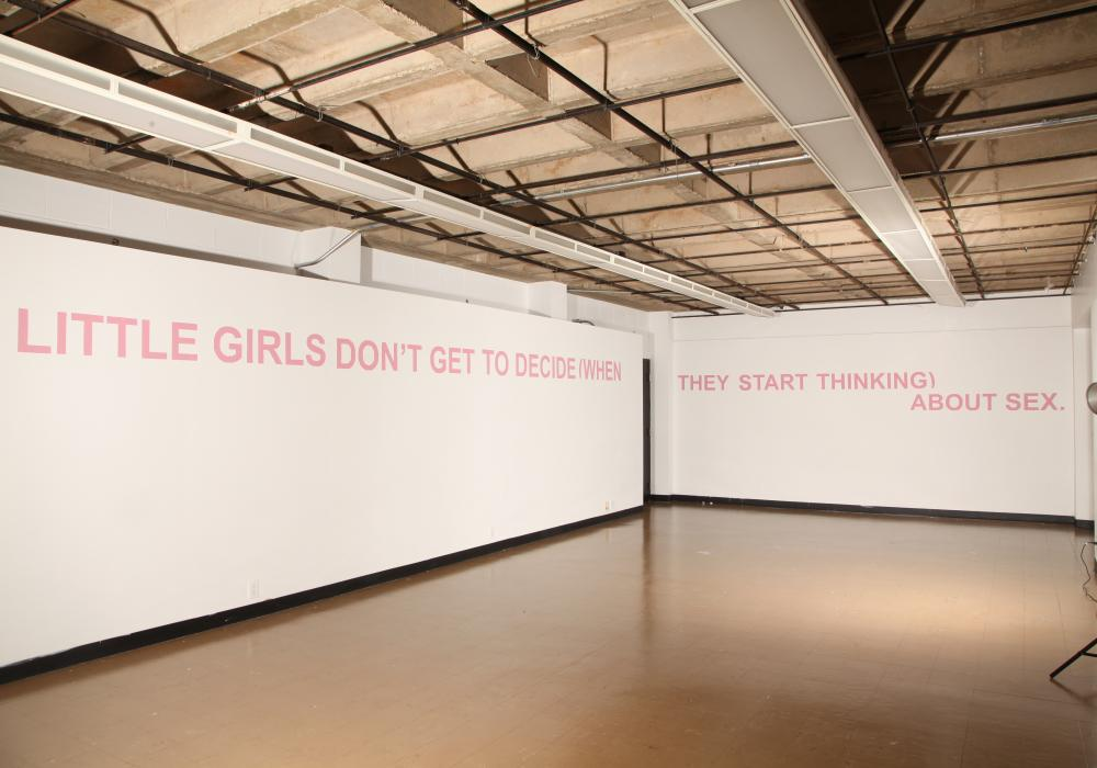 "Image of an empty gallery with concrete floor and white walls. At the top of the walls is pink all-caps text that says ""Little girls don't get to decide (when they start thinking) about sex."""