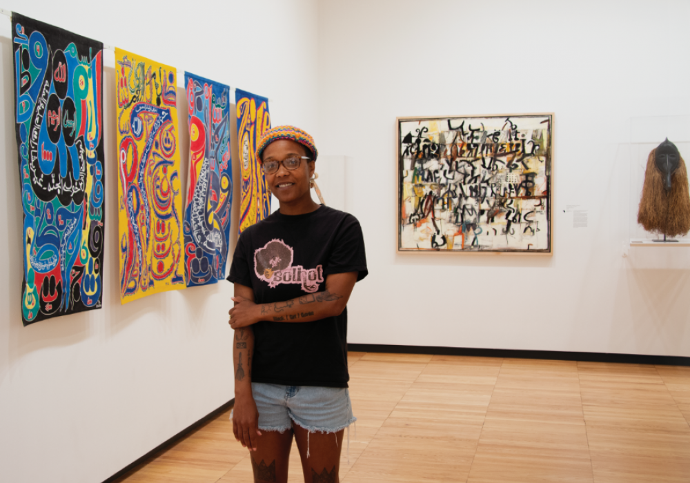 Image of a young black woman with a t-shirt, shorts, and beanie hat standing in the African Gallery at Krannert Art Museum. Behind her are script-based paintings by Yelimane Fall and Wosene Worke Kosroff.