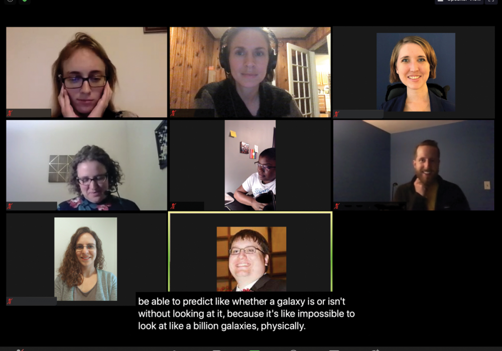"""Eight meeting participants are shown in a grid that would appear on a zoom call or teleconference. There is a caption at the bottom that shows what one participant is saying, """"to be able to predict like whether a galaxy is or isn't without looking at it"""