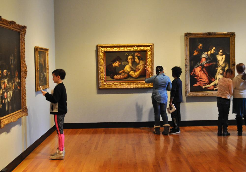 Several children look at several paintings in the Trees gallery at Krannert Art Museum. They are standing individually or in pairs looking at oil paintings by European artists of the 17th and 18th centuries.