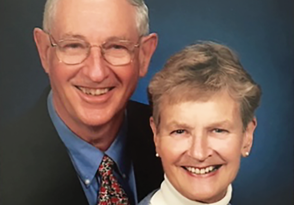 studio portrait of a man and woman smiling with a blue portrait background behind them. The couple is David and Nancy Morse.