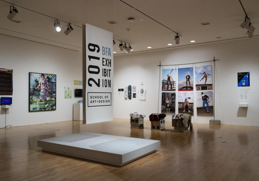 """Photo of a gallery with white walls and colorful artwork, including paintings, posters, and sculpture, with a sign suspended in the middle of the gallery that reads """"2019 BFA Exhibition, School of Art + Design"""""""