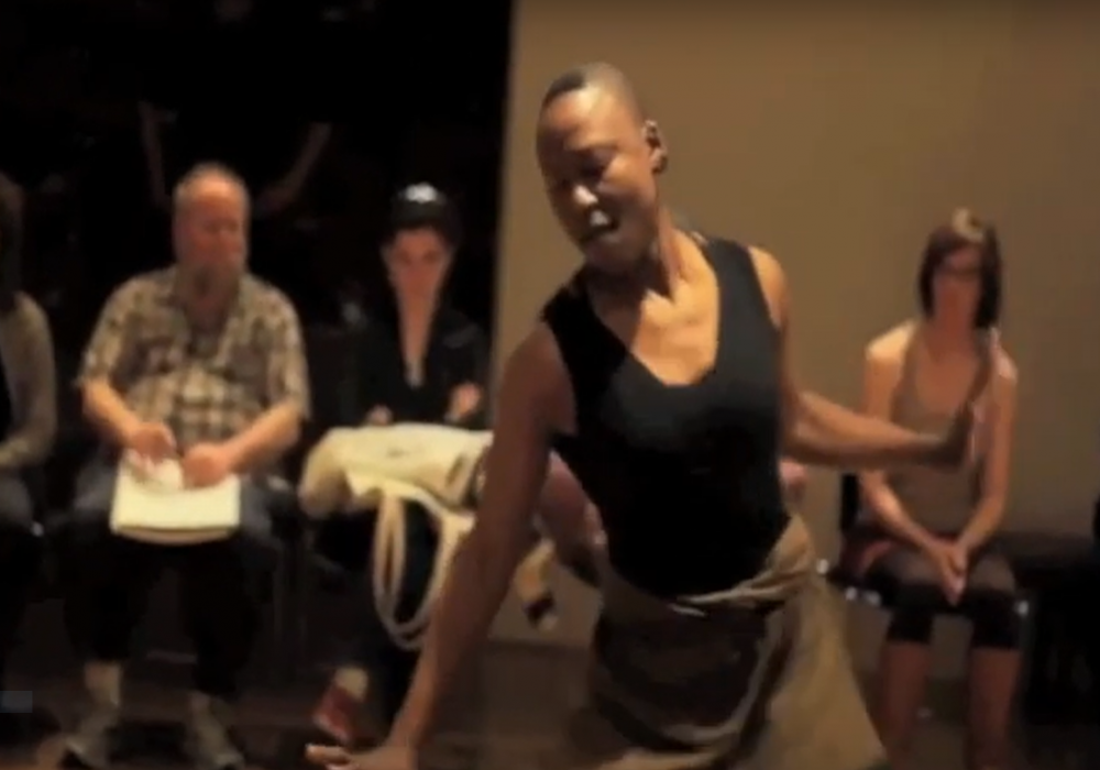 Image of Nora Chipaumire dancing. She is a Black woman with a shaved head dancing in front of a seated audience in a museum gallery. She wears a black leotard and brown skirt.