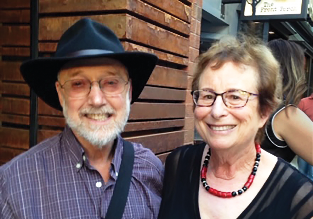 snapshot of a smiling couple in a big city. He wears a hat and they look like they're traveling. They are Gary and Fraeda Porton of Chicago, Illinois.