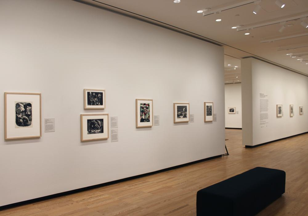Image of a long gallery wall hung with prints. The wall is white and the prints are black and white and color. There is a doorway to an adjacent gallery visible. It has similar artwork.