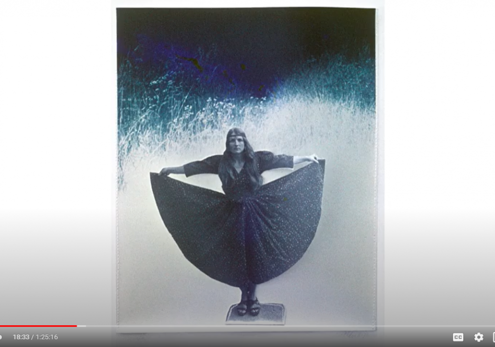 Screenshot of a frame from the Bea Nettles talk at Visual Studies Workshop in Rochester, NY in 1974. It shows a self portrait of the artist in a star covered dress, holding her skirt out to the sides. It is hand-colored in blue tones like night and sky.