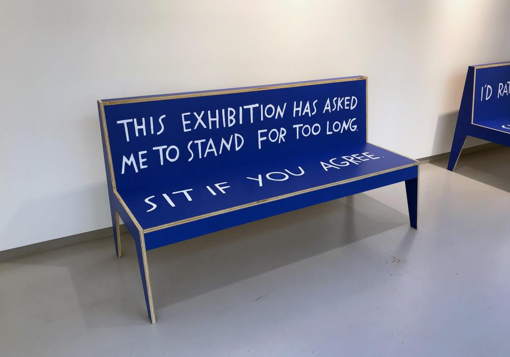 """Blue wooden bench in a gallery with text painted on it. The back of the bench says """"This exhibition has asked me to stand for too long."""" The seat says """"Sit if you agree."""""""