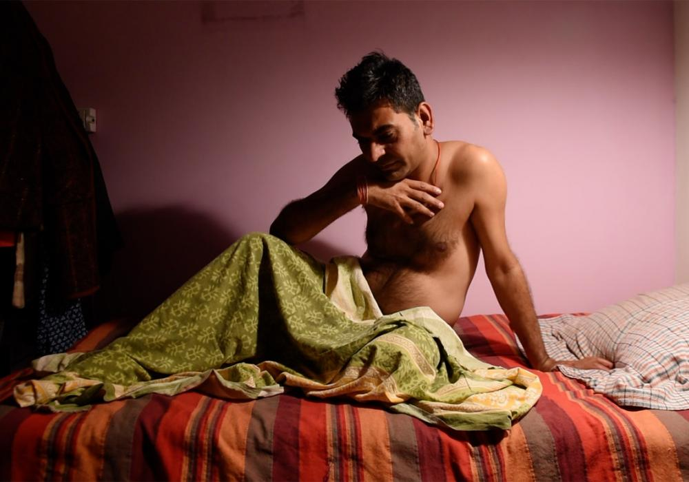 Image of a man propping himself up in bed under colorful bedding. He is emaciated and his face has a pensive expression.