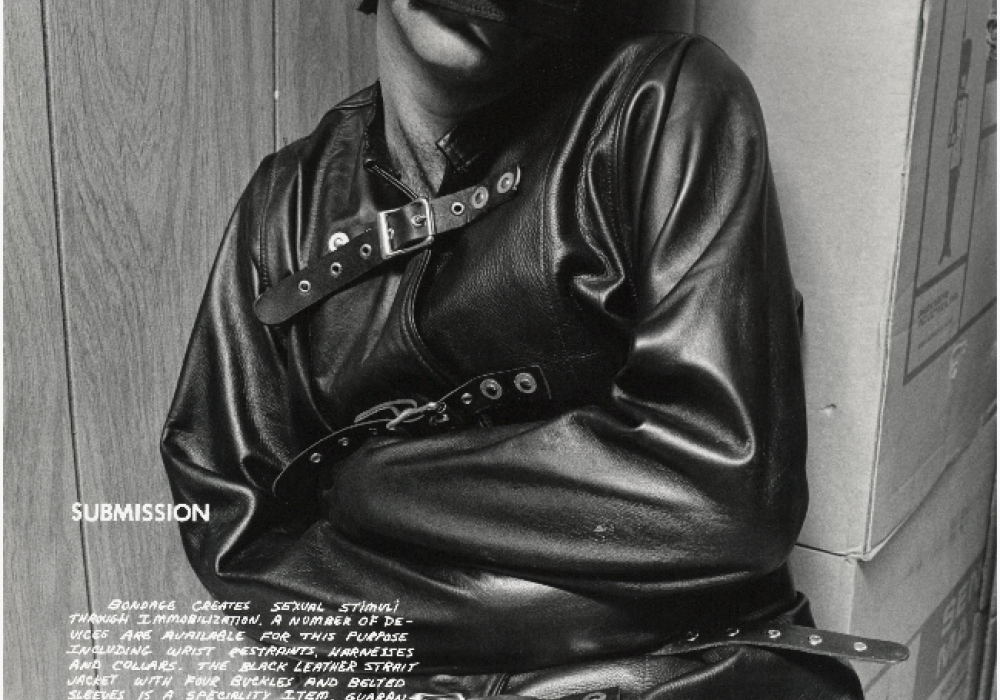 photograph of a man seated in a leather straightjacket and leather hood. text on the photo, titled 'Submission' describes the type of bondage practice being pictured. The man is wearing no pants, only underwear.