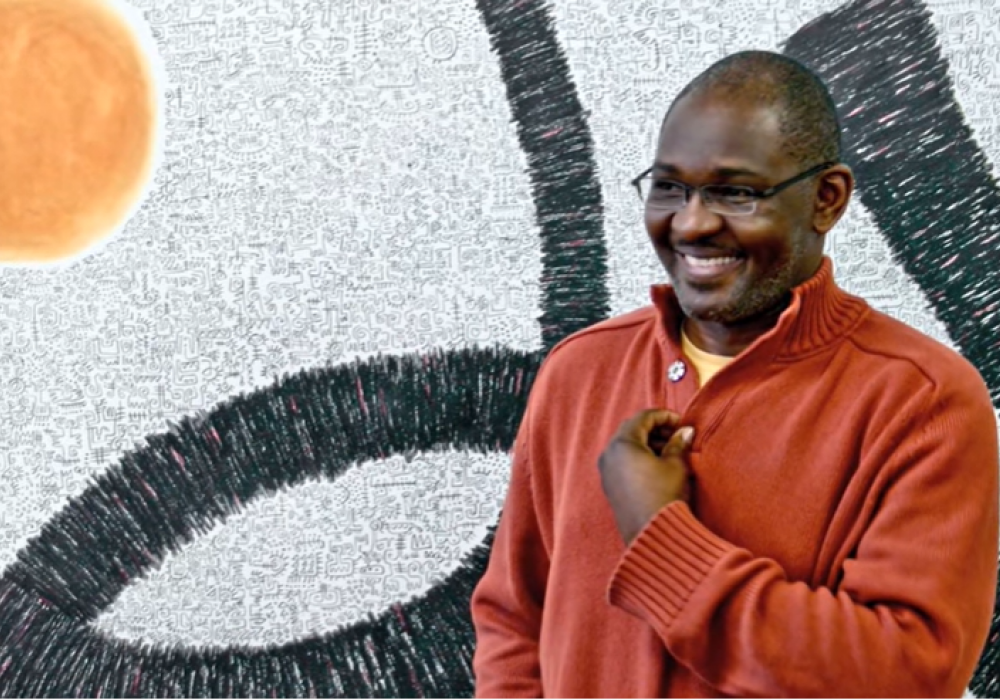 Image of a smiling Nigerian man, the artist Victor Ekpuk, in front of a painting that combines abstraction and nsibidi, a form of script used in his home country.