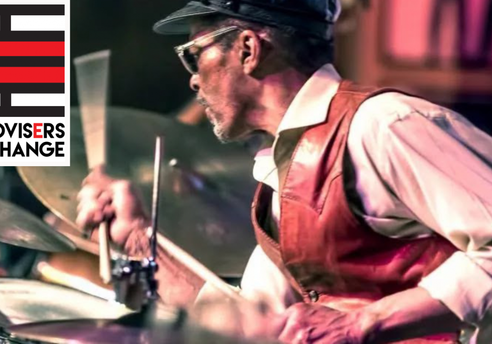 """A black man in a vest and cap plays on a drum set. His hands move so energetically that the drumstick blurs with motion. In the top corner of the image is a red and black striped rectangular logo on a white background. Text says 'Improvisers Exchange."""""""