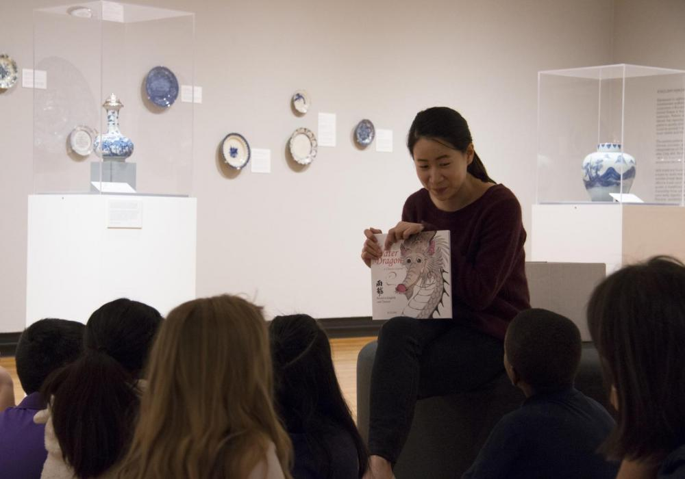 "Graduate Assistant  Sylvia Yang reads a story about dragons to students as they visit the exhibition ""Blue and White Ceramics: An Enduring Global Obsession"" at Krannert Art Museum, 2019."