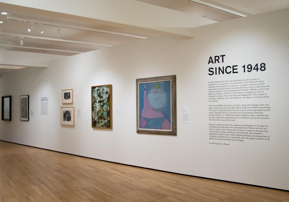 gallery view of entry wall of Art Since 1948 with text and a row of paintings from the museum's modern and contemporary collection. Wall angles toward the viewer to guide their eye down the line of paintings to the next gallery beyond.