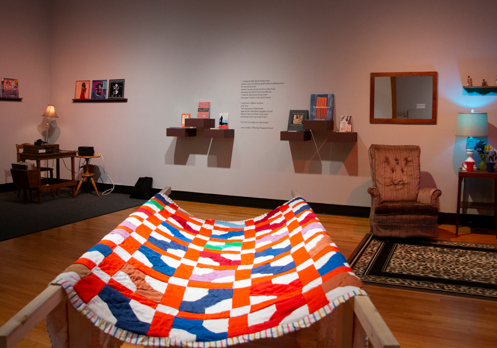 Gallery view of Homemade, with Love: More Living Room, including a colorful quilt in the foreground, music listening station at left, reading area in the center, and furnishings with colored lights at right.