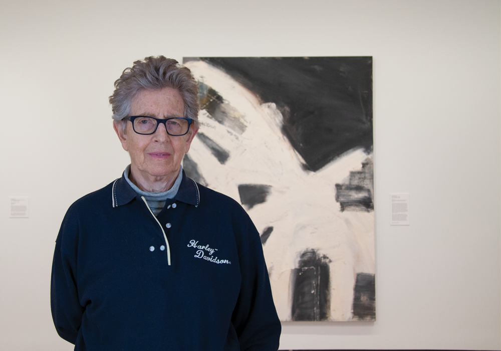 Artist Louise Fishman stands directly facing the camera. She has short, grey hair and glasses and wears a navy Harley Davidson polo. Behind her is a gallery installation of a large, abstract painting Blonde Ambition, with sweeps of white over black.
