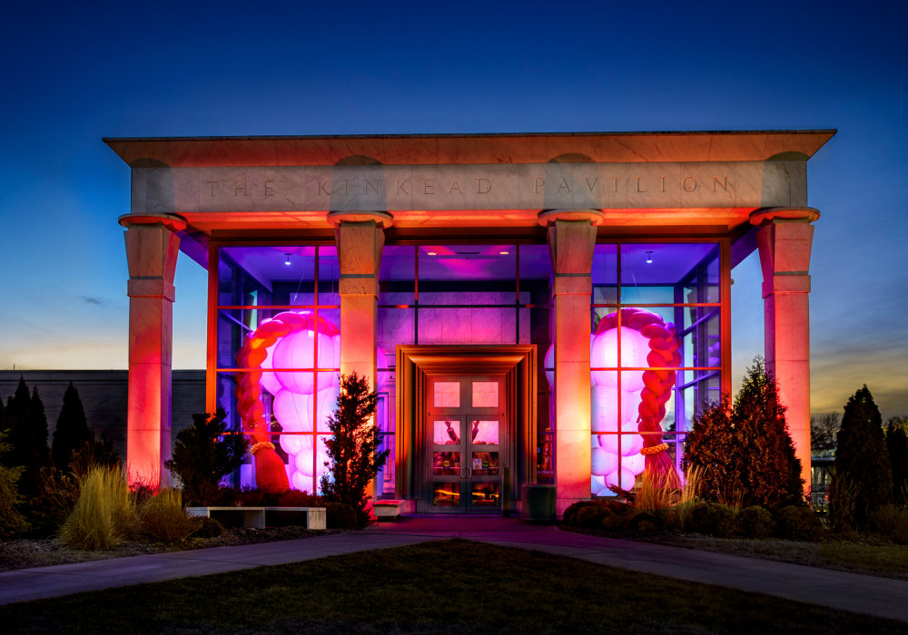 Photo of the temple entrance to Krannert Art Museum at sunset. Two illuminated inflatable sculptures fill the space inside the glass-enclosed entrance to the museum.
