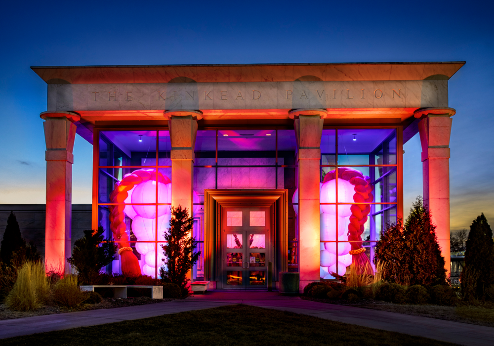 Kinkead Pavilion entrance photographed at sunset. Hive, two lighted sculptures, fill the space symmetrically. Each is pink with a conical structure built of stacked inflated orbs with a long braid that reaches ceiling to floor.