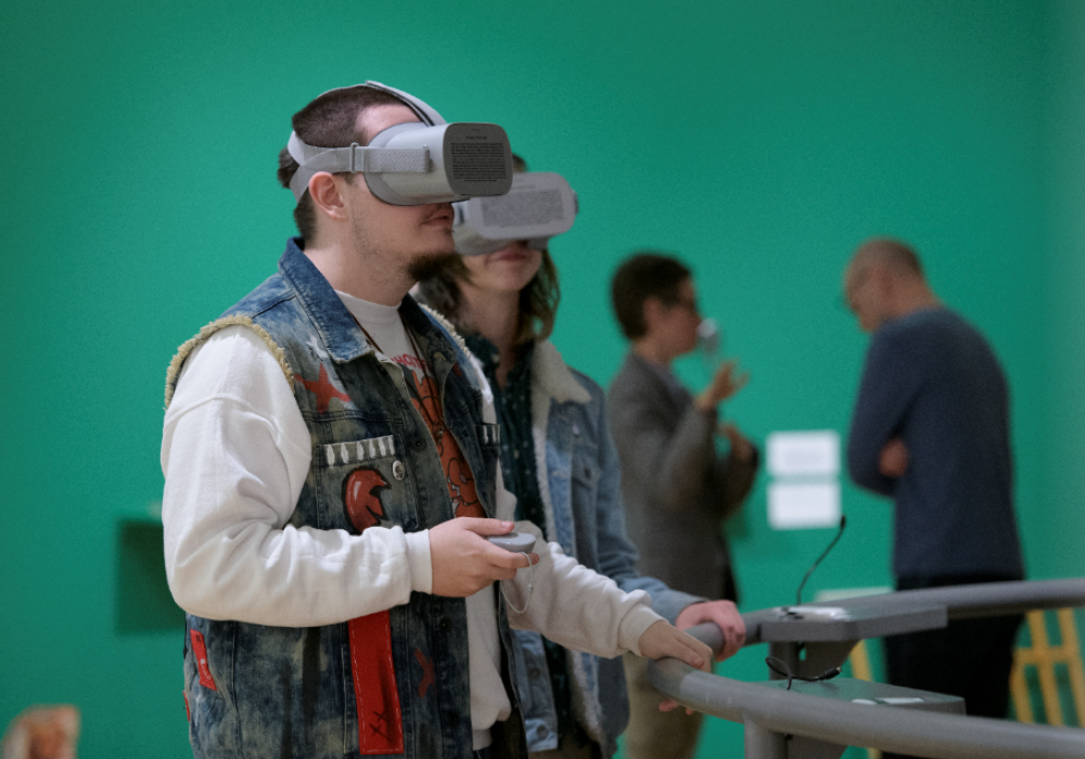 Image of a man and a woman, mid 20s, wearing VR headsets in an art gallery.There is a bright green wall in the background.