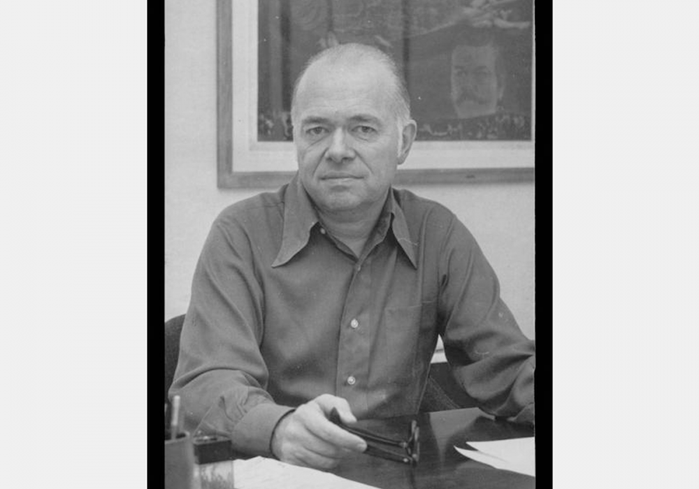 Black and white photograph of George M. Irwin. He wears a collared shirt and is seated at a desk with his glasses in his hand. There is framed art on the wall behind him.