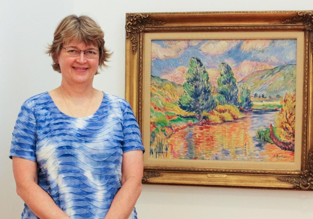 Volunteer docent Ruta Rauber with a favorite American impressionist painting, Catatonk Pond by James P. Butler, in the Bow Gallery at KAM.