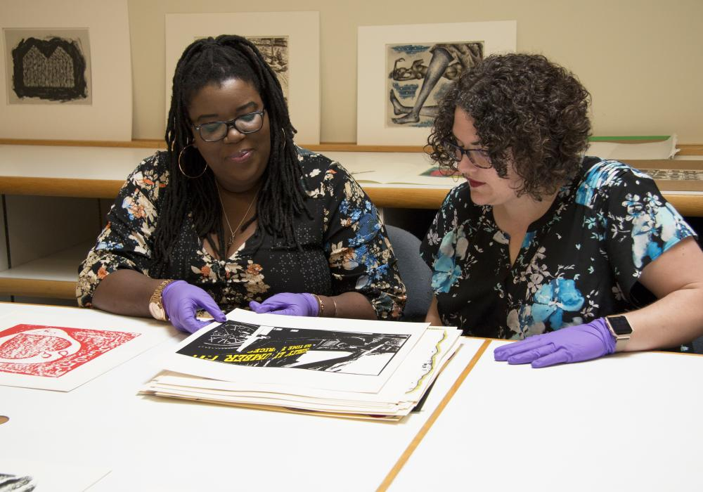 International Fine Print Dealers Association (IFPDA) Curatorial Intern Jamillah Gabriel works with Maureen Warren, curator of European and American Art, to research prints from the 1970 School of the Art Institute portfolio for display in the Moore Galler