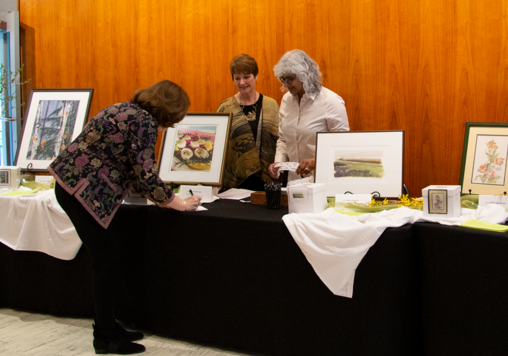 Two older women stand behind a table set with flowers and artwork. Each painting on the table has a box for raffle tickets. A woman on the front side of the table writes out her ticket to participate in the Moms' Weekend Art Raffle.