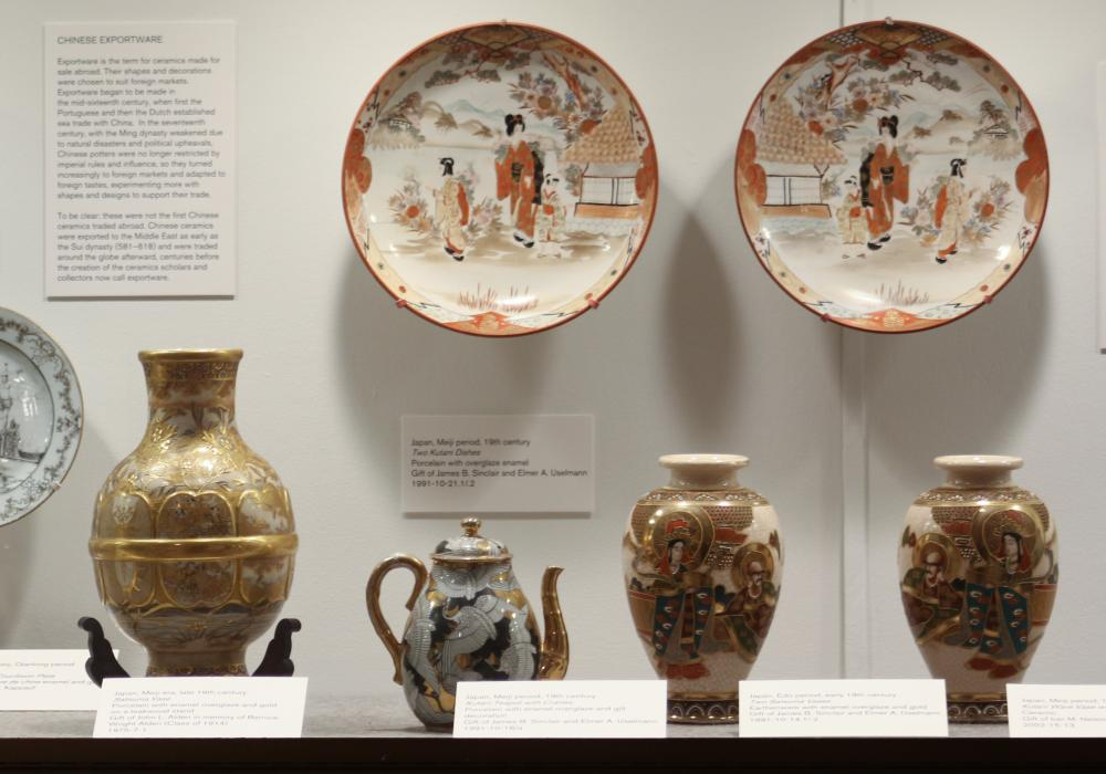 Image of a museum display case filled with intricately painted Japanese ceramics along with a few pieces of Chinese export porcelain. Vases and plates are pictured.
