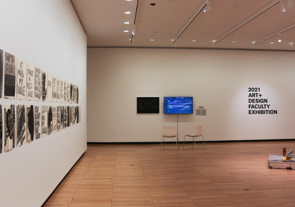 "Installed artwork in Krannert Art Museum's West Gallery, including works on paper, a digital display, and sculpture with the title wall ""2021 Art+Design Faculty Exhibition"""