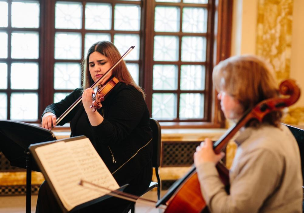 A man plays string bass and a woman plays violin a sunlit room.They read music on music stands and are seated and play with bows. Both are white and 20-25 years old.