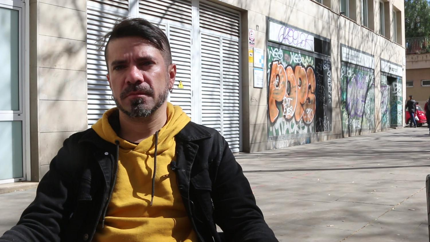 Color photograph of a man in a jacket and hooded sweatshirt. He squints from the bright sun, his face is serious. The photo is taken with an empty sidewalk and closed storefronts covered in graffiti tags in the background.