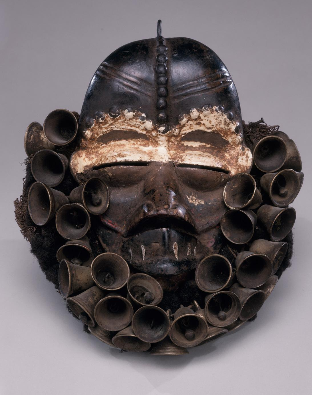 """Singer"" dance mask, early 20th century Ivory Coast (We) Wood, bells, fiber, chalk 11 3/4 x 9 1/2 inches Gift of Richard J. Faletti Family Collection 2000-5-1"