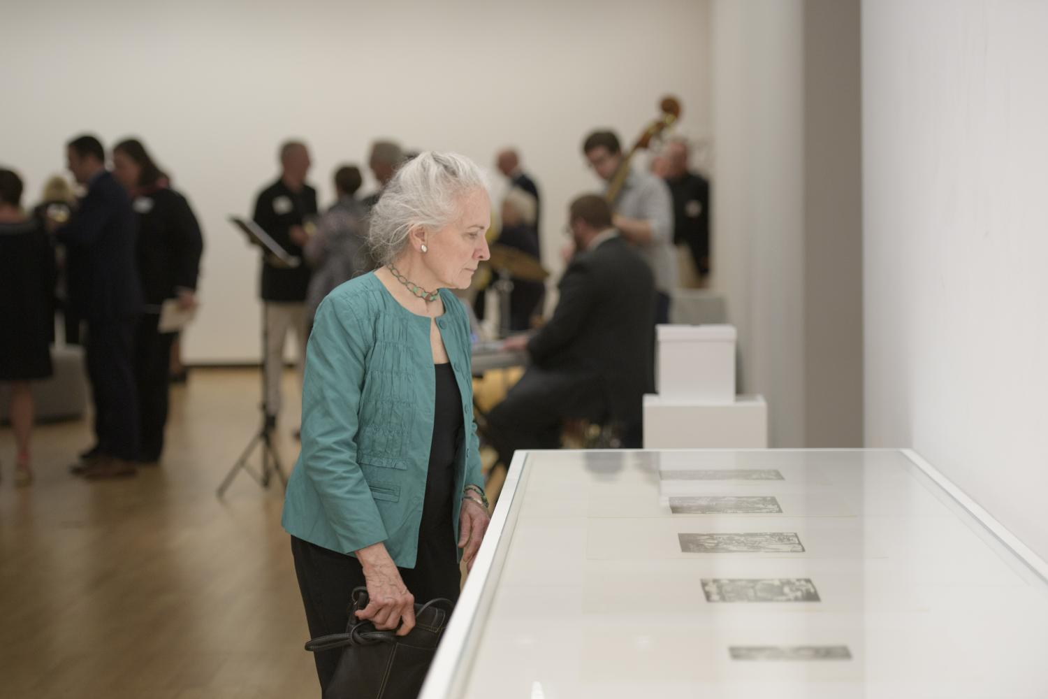 A guest views artwork by Hale Woodruff proposed for acquisition at the Acquired Taste Celebration at Krannert Art Museum, May 18, 2019. Photo by Della Perrone