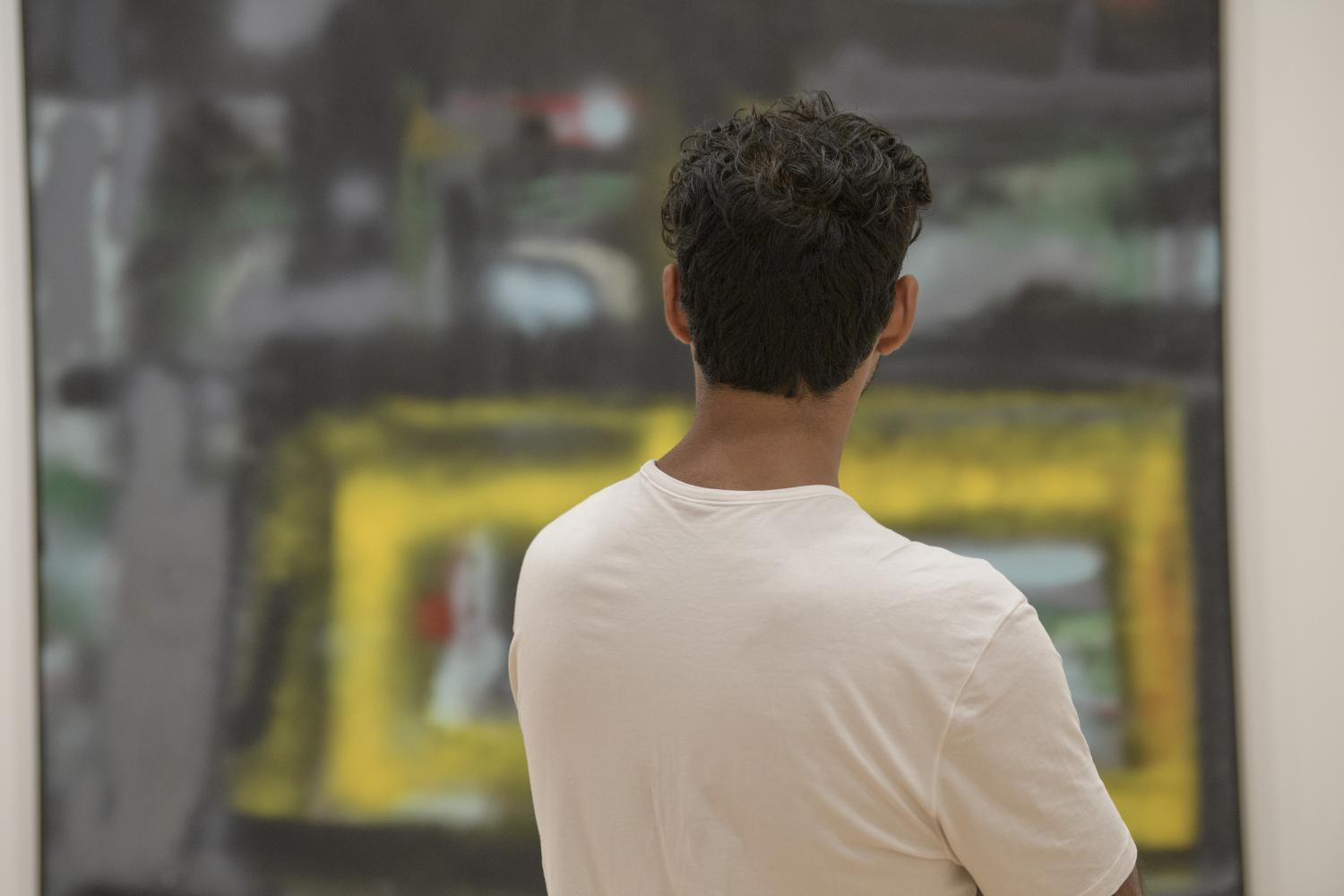 A male student with his back to the camera looks at NY Road by Hedda Sterne in Art Since 1948 at Krannert Art Museum