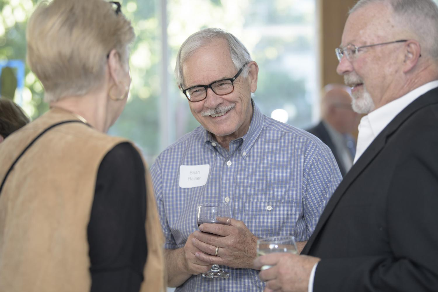 Three friends, a woman and two men, talk and laugh at the member reception at Krannert Art Museum