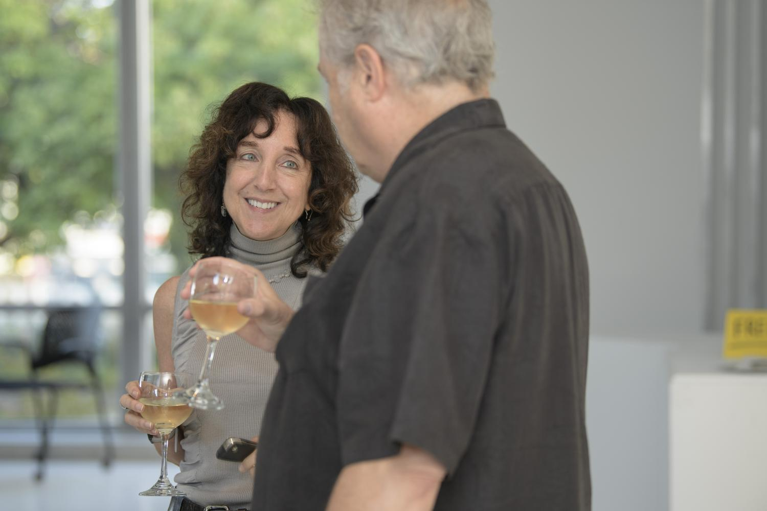 Photo of two people holding wine glasses and smiling at one another.