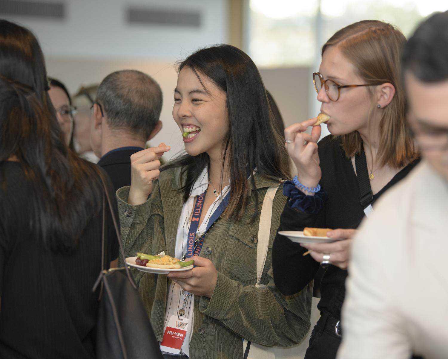 Two female students talking and eating at a museum reception. Theyare in a crowd
