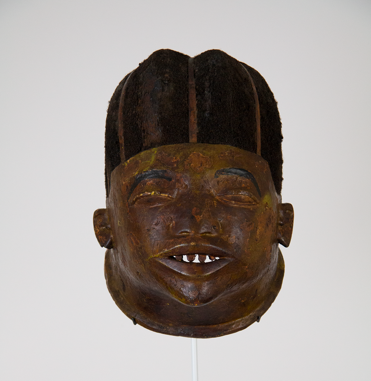 Wooden mask that resembles a wide-faced man with hair and a cap or crown. The face of the mask is painted yellow and the paint is chipped. You can see light through the mouth, which has carved teeth.