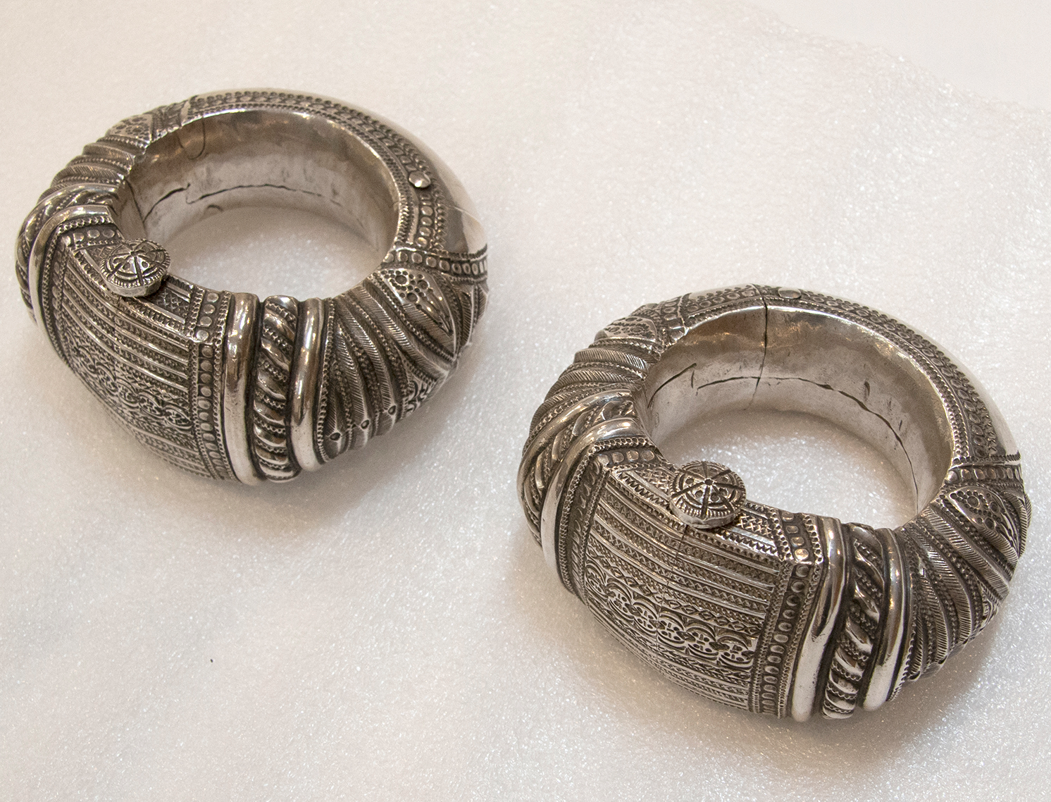 Pair of thick silver anklets from Oman or Zanzibar. They are decorated with textures that resemble folded or embroidered fabric and have a button at the top that serves as a clasp to close them around the ankle of the wearer.