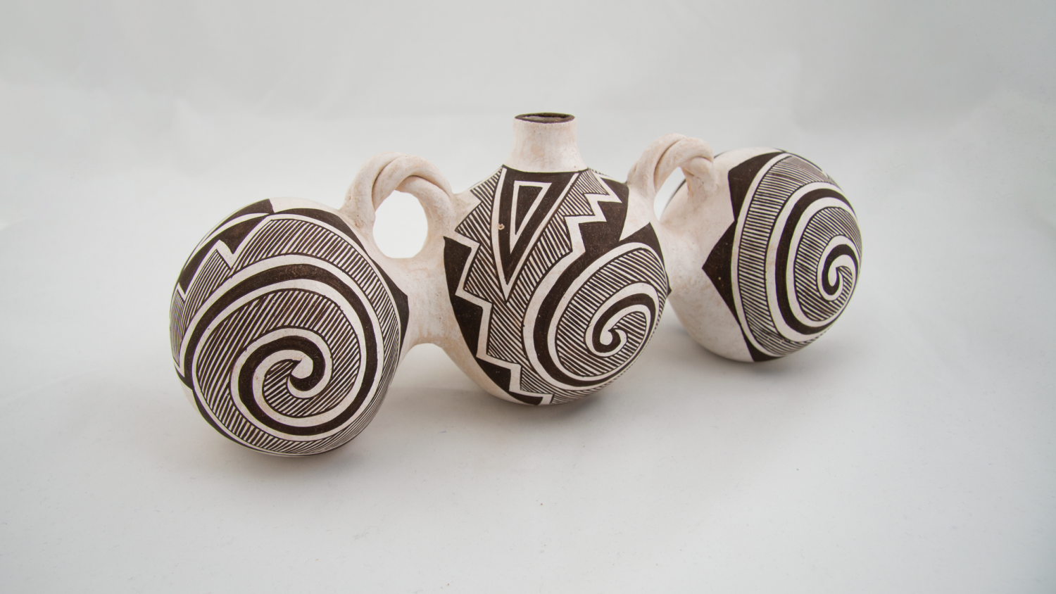 ceramic jar with three linked spherical sections, connected in a straight line, called a triple canteen. It is white with black decoration, and all three sections bear similar designs with concentric circles. A necked opening rises from the center canteen