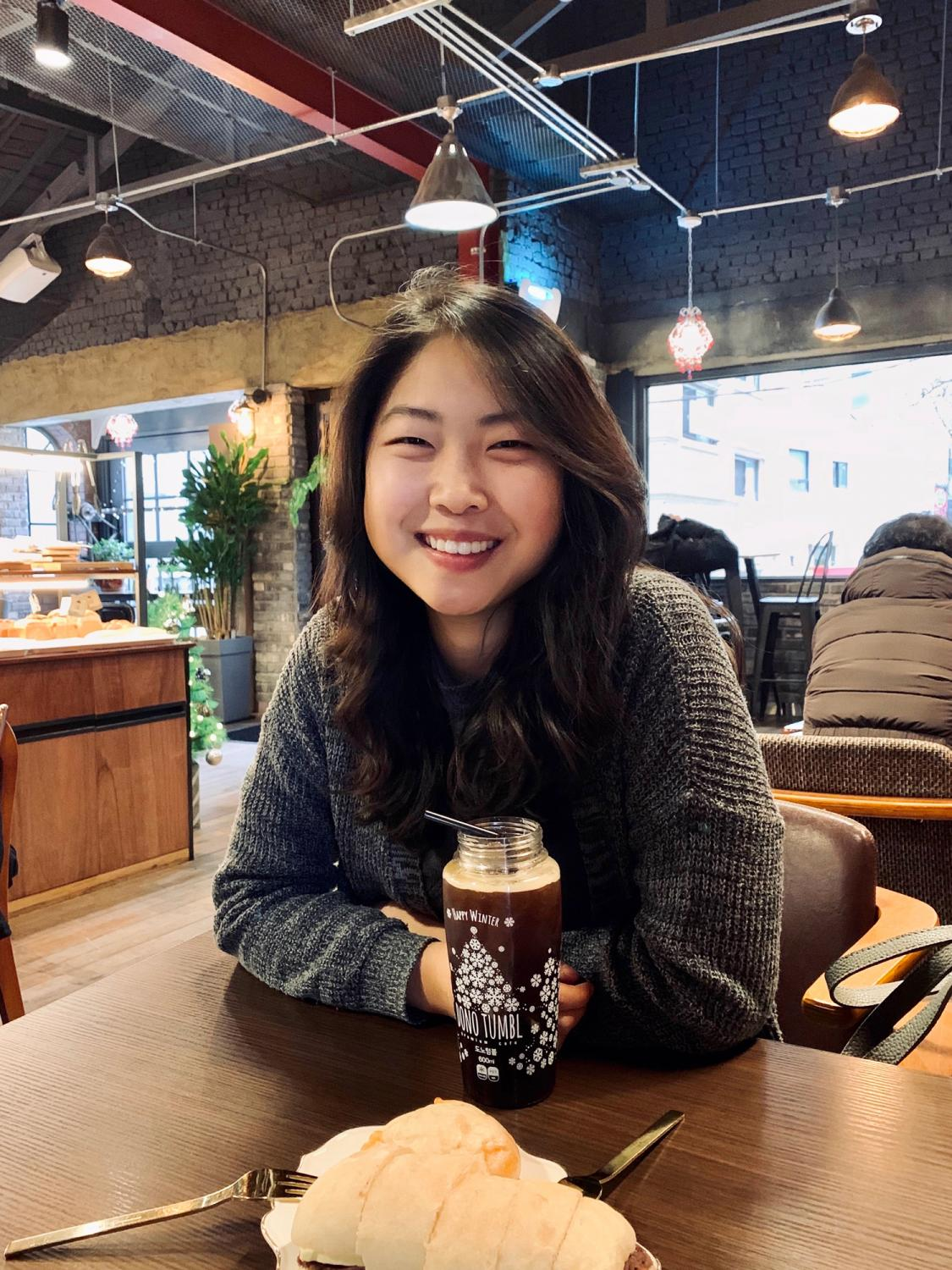 Image of a young woman of Asian descent, smiling in a coffee shop. Her torso and head are visible, and she is leaning her forearms on the table in front of her.