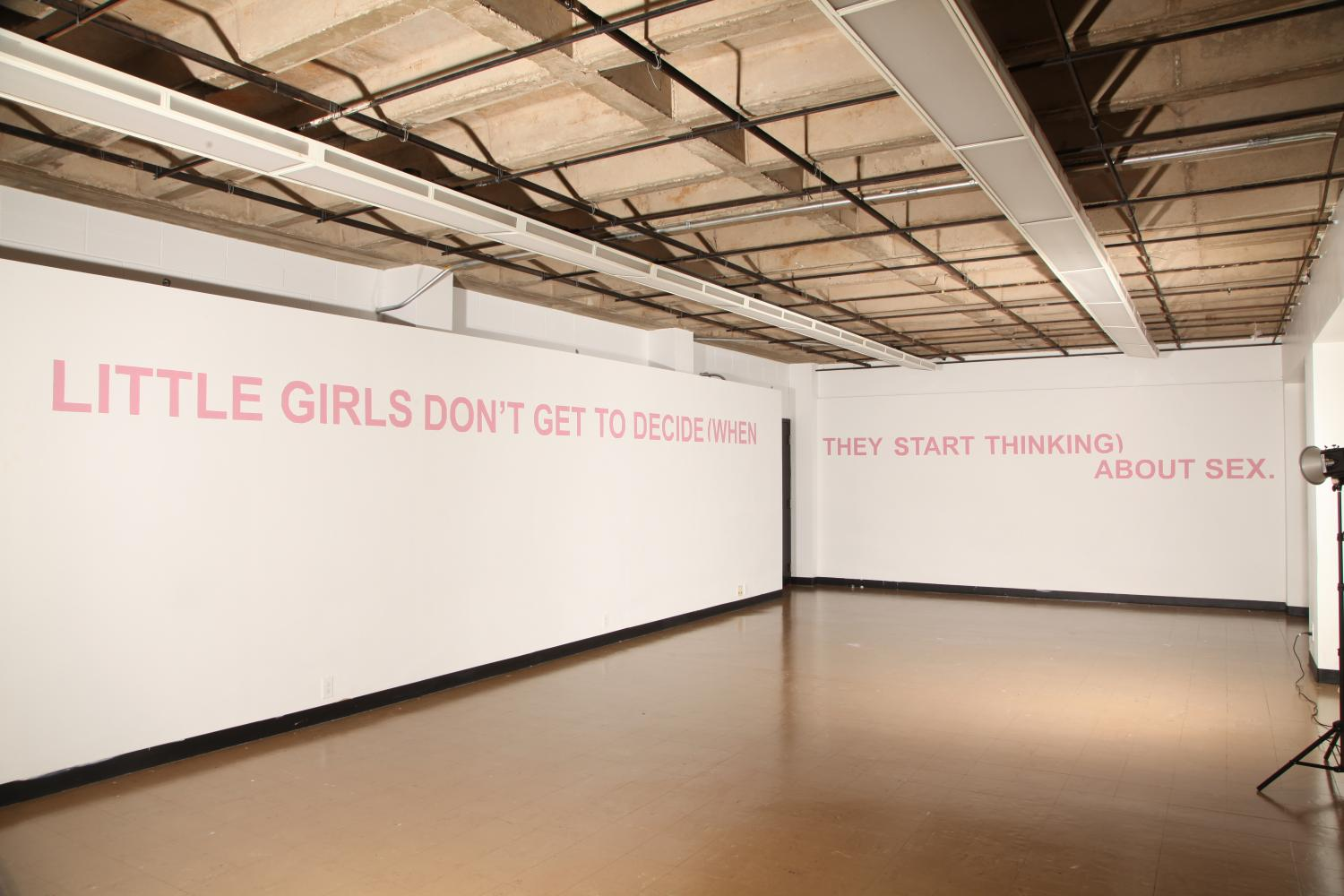 """Image of an empty gallery with concrete floor and white walls. At the top of the walls is pink all-caps text that says """"Little girls don't get to decide (when they start thinking) about sex."""""""