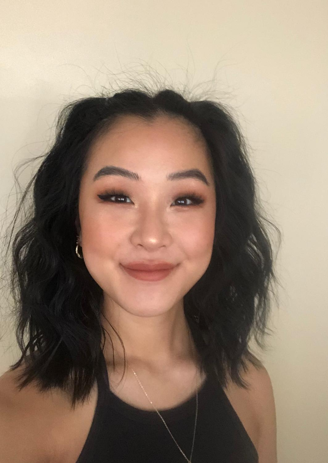 Head and shoulders portrait of a young woman of Asian descent. She is smiling and has wavy dark hair pulled back from her face in barrettes. She is wearing a black tank top.