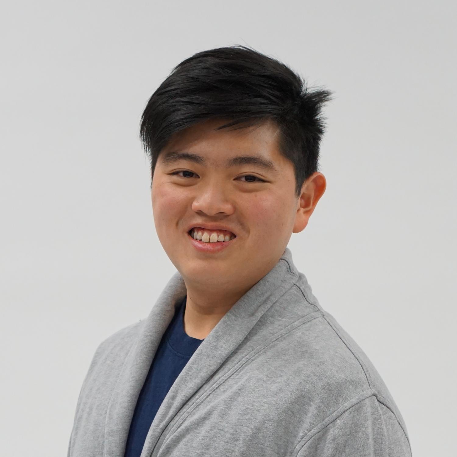 Professional headshot portrait of a young man with dark hair and Asian features, the designer Aspen Tng. He is slightly turned to the side and smiling.