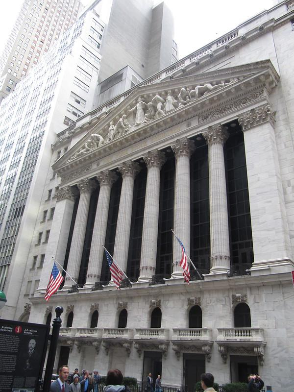 The picture was taken from the front side of the New York Stock exchange building. The building is white and decorated with columns and arched doors.